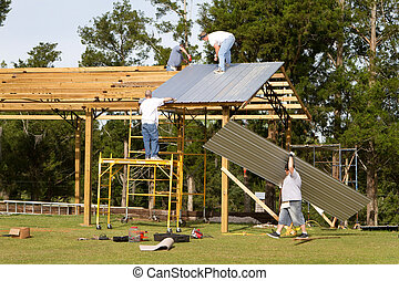 Four construction workers apply corrugated metal sheets to the rafters of a pole barn by fastening with screw-guns.