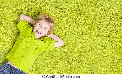 barn, liggende, hen, grønne, carpet., glade smile, barnet, dreng, fem ældre år, top udsigt