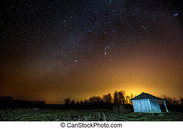 Barn under starry sky at night