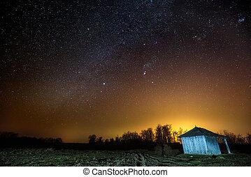 Barn under starry sky at night