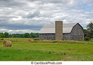 barn with hay bales - Old barn with silo and hay bales.