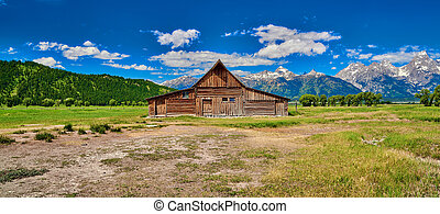Barn with the Grand Teton mountains and blue sky at Grand Teton National Park.