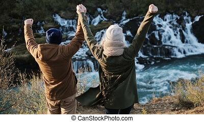 barnafoss, islande, couple, mains arrière, jeune regarder, chute eau, ensemble., jumpimg, heureux, élévation, vue