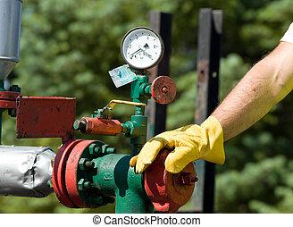 Barometer - Oil worker examining barometer on oil plant