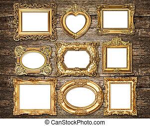 Baroque style golden frames over wooden background. Antique obje