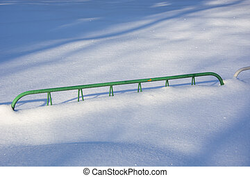 Barrage for an attraction with a snowdrift. She poured a lot of snow on the fence. Winter day in the city recreation park.