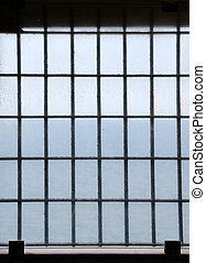 Barred prison window with ocean view.
