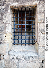 Barred window in the stone wall of the castle Santa Barbara, Alicante, Spain