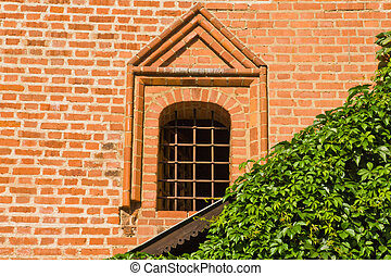 barred window on the wall of an old manor