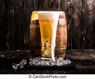 barrel and glass of light beer with ice and lemon