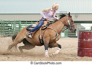 Barrel Racer - Beautiful blonde cowgirl riding a gorse in a...