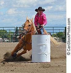 Barrel Racing - Beautiful cowgirl on a palomino horse barrel...