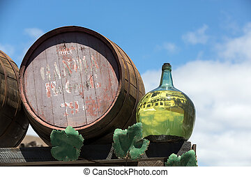 Barrels and big bottles with grape wine - malvasia. ...