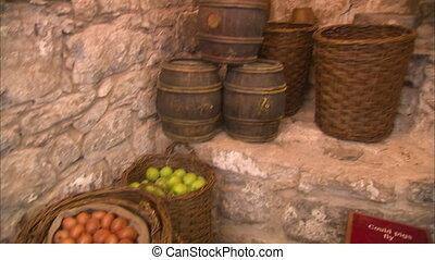 A tilt down shot from alcohol barrels to fruits.