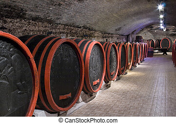 Barrels in a wine-cellar. - Antique wooden barrels in an old...