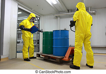 Two specialists in protective uniforms, masks, gloves and boots transport barrels of chemicals on forklift in factory