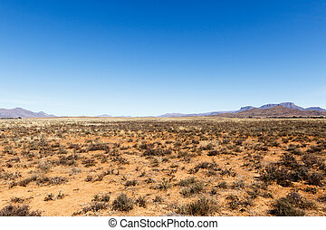 Barren field with mountains and blue sky