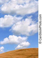 Blue sky and cumulus clouds above a curved barren drought ridden hillside.