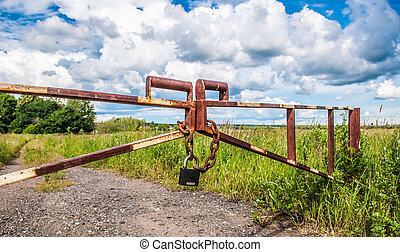 barrier in a field on the lock with a chain