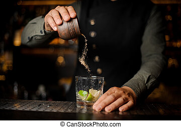 Bartender adding cane sugar into the cocktail glass with lime. Process of making Caipirinha cocktail