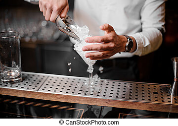 Bartender adding crushed ice into an empty cocktail glass