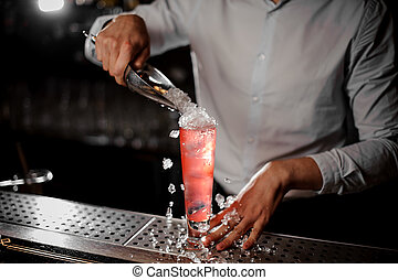 Bartender adding crushed ice to the transparent red cocktail