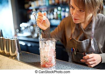 bartender adding essence to cocktail glass at bar