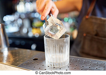 bartender adding ice cube into glass at bar
