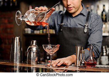 Bartender adding red alcoholic drink into cocktail glass