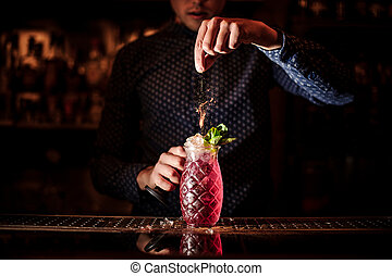 Bartender adding spices into the fresh and sweet strawberry mojito summer cocktail