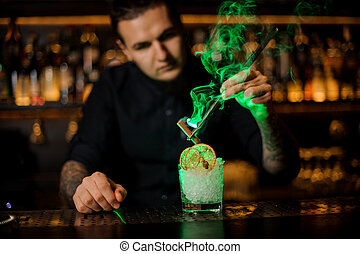 Bartender adding to a glass with dried orange and ice a smoked cinnamon with tweezers
