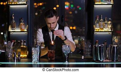 Bartender burning orange peel for cocktail - Professional...