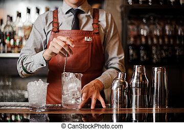 Bartender cooling out Cocktail glass mixing ice with a spoon