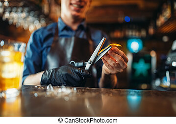 Bartender cut rind from oranges at the bar counter - Male...