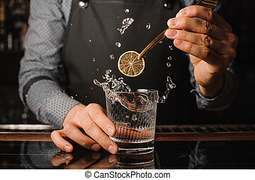 Bartender decorating a glass with splashing drink