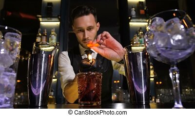 Bartender finishing preparation of cocktail drink - Closeup...
