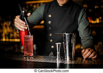 Bartender finishing preparing cocktail at bar counter