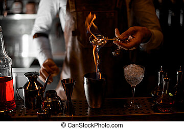 Bartender firing up alcohol in bar spoon