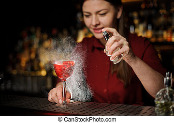 bartender girl adds peat whiskey to alcoholic cocktail