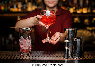 Bartender girl serving a light red cocktail