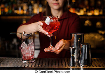 Bartender girl serving a red campari cocktail