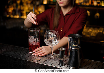 Bartender girl stiring a fresh red cocktail