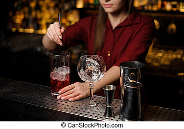Bartender girl stiring a light red cocktail