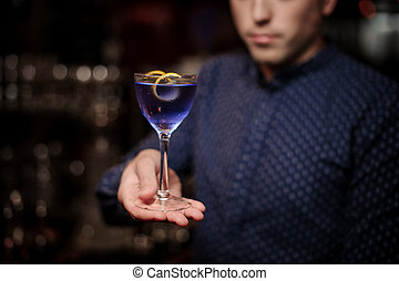 Bartender holding a glass of violet cocktail decorated with an orange pill