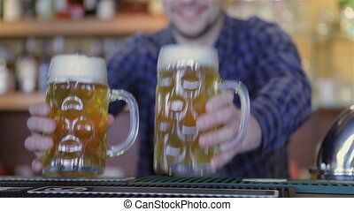 Bartender holding beer glasses and smiling