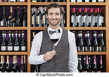 Bartender Holding Red Wine Glass Against Shelves