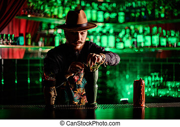 bartender in hat neatly decorates with plant glass with ice cocktail on the bar