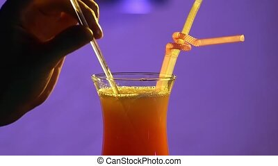 Bartender is finishing cocktail, decorate it with slice of orange, tubules, on purple