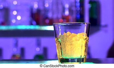 Bartender is making cocktail at bar counter in dark, shots,...