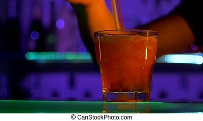 Bartender is making cocktail, pouring at bar counter, mixing with  tubules in dark, shots, slow motion, close up